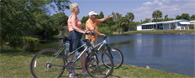 Bikers enjoying the view of the lake at Club Wildwood manufactured home community in Hudson Florida