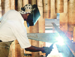 Man welding in a Jacobsen Homes manufactured home factory
